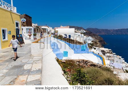SANTORINI ISLAND CRETE GREECE - June 29 2013: View of Fira town. White concrete staircases leading down to beautiful bay with clear blue sky and sea in Santorini island