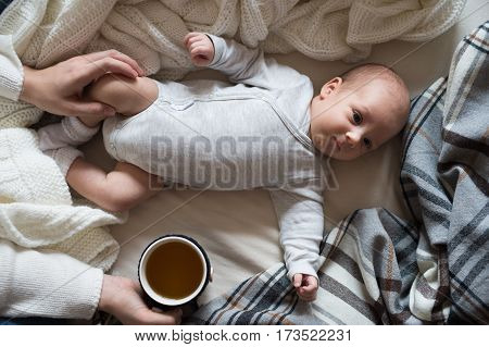 Unrecognizable mother holding a cup of tea and her newborn baby son lying on bed next to her