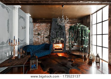 Interior with fireplace, candles, skin of cows, brick wall, large window and a metal cell of a loft, living room, coffee table and dark blue sofa in modern design.