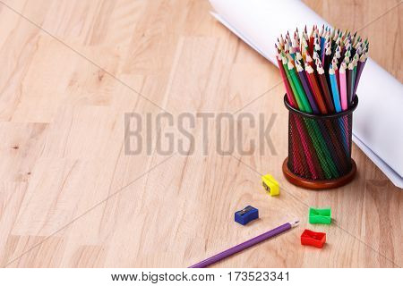 Stationery and paper on the table. Plank table with accessories to study. The lesson. Pencil, sharpener and paper on the table. Space for text. School life. Education. Stationery glass with colorful pencils. Drawing.