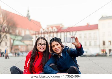 Two girlfriends taking a self portrait, sitting on the street in a touristic city center, while visiting the city and having fun.