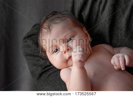 Newborn Baby On A Black Background.  Baby Resting In Mother's Hand. Newborn Concept And The Concept