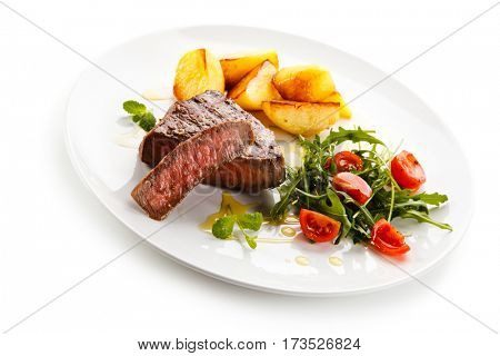 Grilled steaks, baked potatoes and vegetables