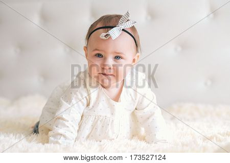 Сute 7 month baby-girl crawling on bed.Сlose-up portrait kid wearing nice head accessory at home.