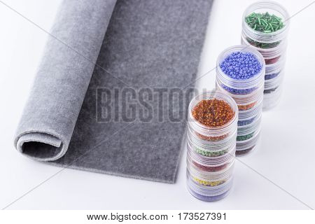 Seed beads in glass tubes and grey beading mat for jewelry making and beading process on white background. Selective focus.
