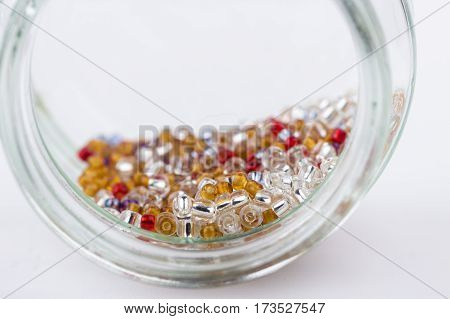 Mix of colored glass seed beads for jewelry making and beading projects on white background. Selective focus.