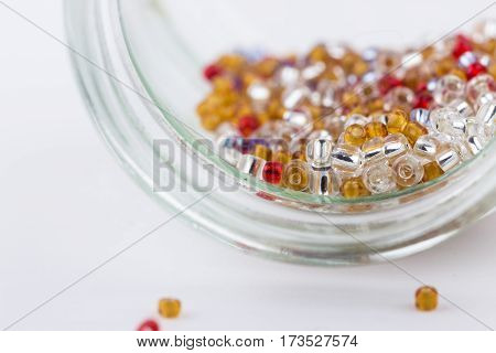 Colored glass seed beads mix for beading closeup on white background. Selective focus.