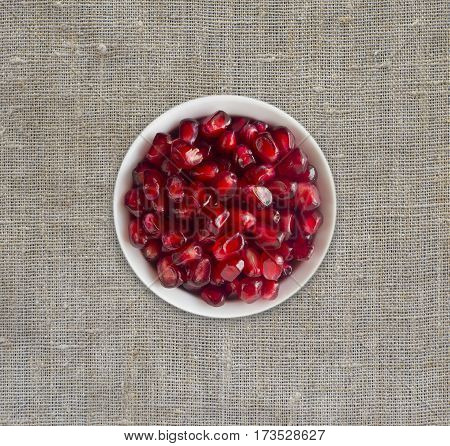 Red grains of a pomegranate in ceramic bowl. Pomegranate seeds on a linen tablecloth. Top view. Sweet and juicy berry with copy space for text.