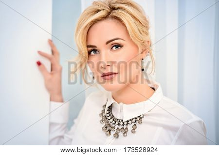 Beautiful woman with blue eyes and blonde hair wearing white blouse and necklace. Beauty, fashion concept. Luxurious lifestyle. Jewellery.