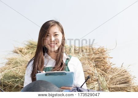 young chinese woman agronomist working on motocycle with golden straw