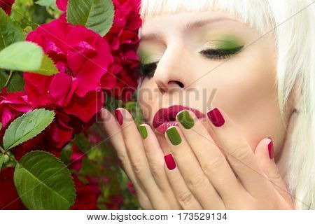 Trendy red green blue manicure and makeup on the blonde with a rose in her hand.