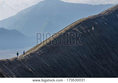 tourist walking on an edge of volcano crater at Bromo Mountain, Tengger Semeru national park, East Java, Indonesia.