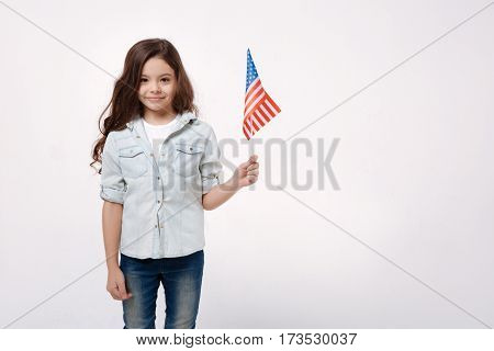 Proud to be the USA citizen . Joyful happy cheerful girl holding the American flag while smiling and standing against white background