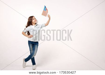 Proud little citizen. Joyful charismatic cute girl holding the American flag while expressing positivity and standing isolated in white background