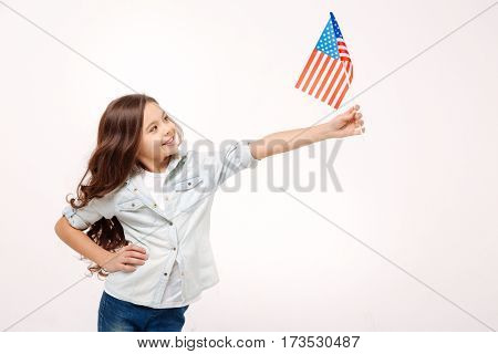 Happy little citizen. Joyful charming cute girl holding the American flag while expressing positivity and standing isolated in white background