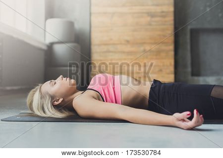 Young slim blond woman in yoga class lay on floor. Girl do meditation corpse pose, savasana for relaxation. Healthy lifestyle in fitness center. Closeup
