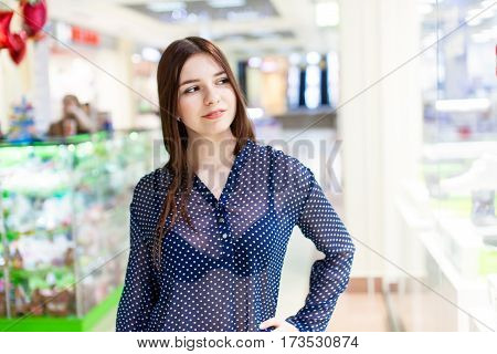 Happy smiling teenage girl standing in shopping center