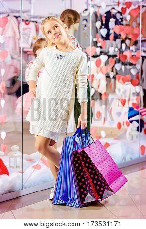 Happy little girl goes shopping. Kid's fashion. Modern children. Seasonal sale, shopping.