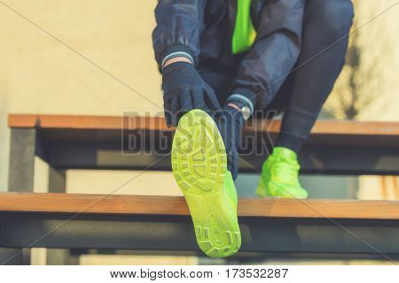 Urban jogger stretching on the bench in park.
