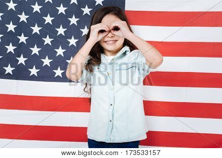 Fooling around. Joyful smiling amused girl having fun and expressing happiness while standing against American flag