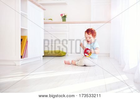 Cute Ginger Baby Boy Playing With Toys In Bright Kitchen, At Home