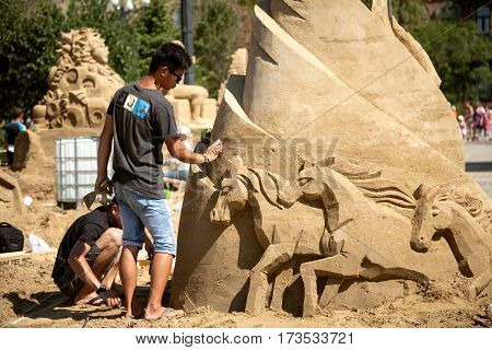 Khabarovsk Russia - August 30 2014: Sand sculpture festival - two young artists working on a horse figure. Outdoor beach art competition