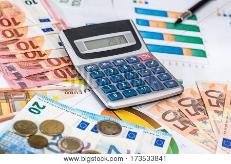 Euro Bills With Calculator And Pen On Financial Settlement With The Charts.