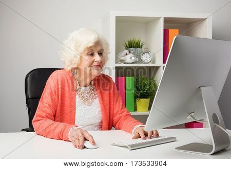 older woman working in the office on  computer