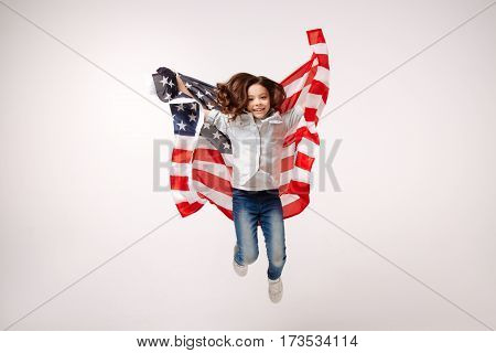 Sharing positive mood. Joyful flexible smiling girl having fun and expressing joy while jumping against white background and holding the American flag