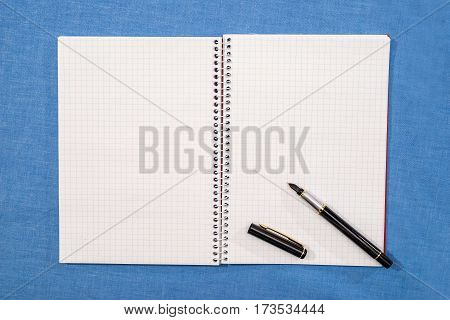 pen lies on empty pages of a notebook.