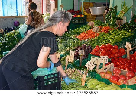 HERAKLION, CRETE - SEPTEMBER 19, 2016 - Cretan stallholder sorting vegetables on a market stall in the city centre Heraklion Crete Greece Europe, September 19, 2016.