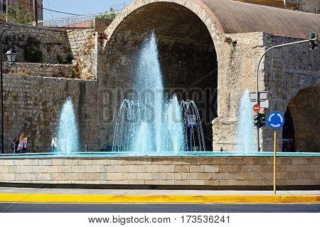 HERAKLION, CRETE - SEPTEMBER 19, 2016 - View of the fountain on Leof Nearchou with Neoria dockyards buildings to the rear near the port Heraklion Crete Greece Europe, September 19, 2016.