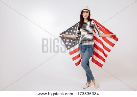 Lets unite. Artistic smiling charming woman expressing positivity while standing against white background and holding American flag
