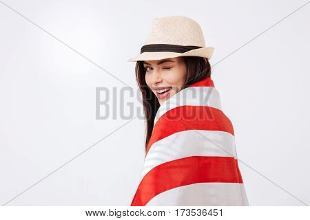 Join my celebration. Playful smiling charismatic woman expressing happiness and winking while standing isolated in white background and holding American flag