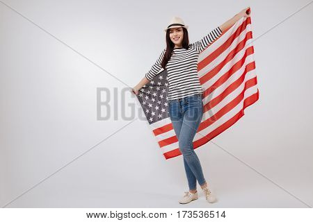 Happy citizen of multicultural country. Graceful delighted charismatic teenager smiling and celebrating national holiday while standing against white background and holding American flag