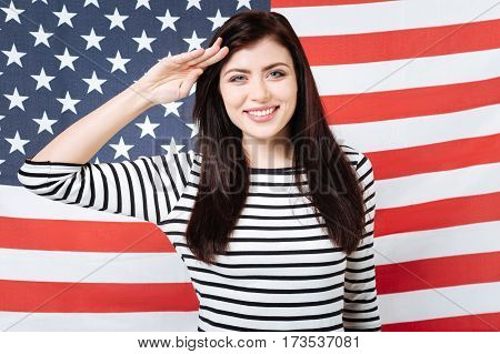 Loyal citizen of the country. Happy delighted lively woman smiling and celebrating American holiday while standing against American flag and putting hand to her temple