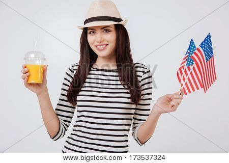 Lets spend this holiday together. Happy cheerful merry woman smiling and celebrating American national holiday while standing against white background and holding American flag and glass of juice