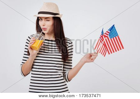 Enjoying every moment. Artistic cheerful merry woman smiling and celebrating American national holiday while standing against white background and holding American flag and drinking juice