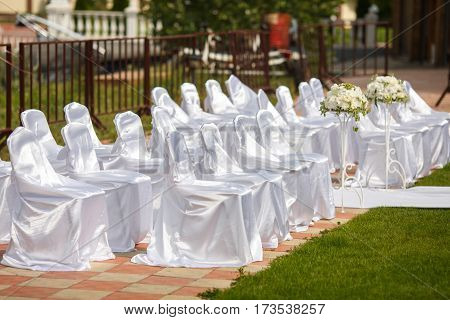 Chairs Dressed In White Satin Wait For Guests Of A Wedding