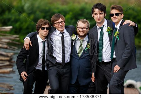 Stylish dressed groom and groomsmen pose together by the river