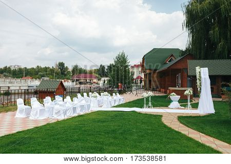 White chairs for guests stand before the wedding altar on an open air