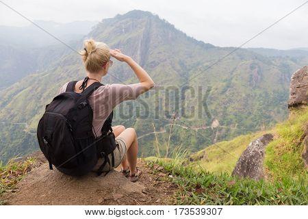 Woman enjoying pristine nature and beautiful view of tea plantations from the top of Small Adams peak near Ella, Sri Lanka. Tracking outdoors tourist adventure.