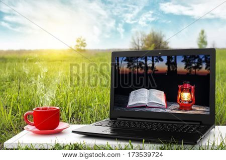 Laptop and cup of hot coffee on the background picturesque nature, outdoor office. E-book library concept with laptop computer and book. Old books on a wooden shelf. Travel concept. Business ideas.