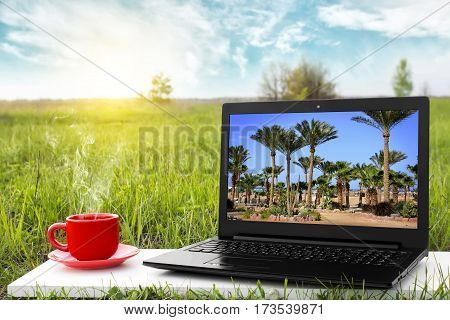 Laptop and cup of hot coffee on the background picturesque nature, outdoor office. Travel concept. Business ideas. Choice of travel.