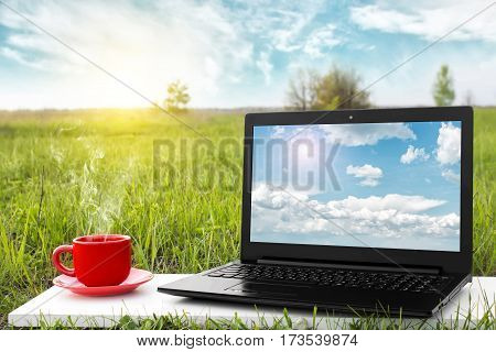 Laptop and cup of hot coffee with blank screen on the background beauty nature, outdoor office. Travel concept. Business idea. Choice of travel. Traveling by airplane. Copy space. Advertising airline.