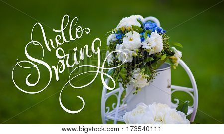 Bouquet of roses hydrangea on decorative metal stand and text Hello Spring. Calligraphy lettering.