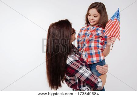 Sharing our love and care. Careful smiling delighted mother holding her daughter and celebrating American national holiday while standing against white background