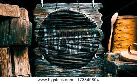 Honey in birch bark box on wood stump. Other stumps in stack. Round wood sign with text 'Honey'. Isolated over black