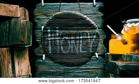 Honey in glass jars on wood stump. Other stumps in stack. Round wood sign with text 'Honey'. Isolated over black