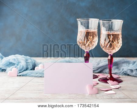 Two stemmed champagne glasses with pink hearts blank paper note card to fill with your text on wooden textured background. Valentine's day wedding romantic date invitation
